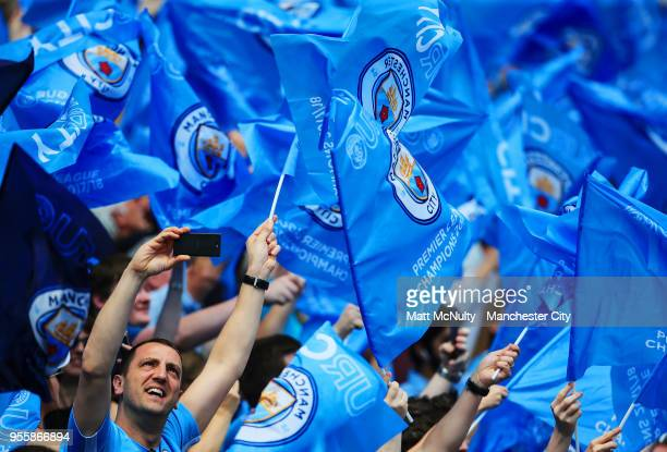 Manchester City fans wave flags before the Premier League match between Manchester City and Huddersfield Town at Etihad Stadium on May 6 2018 in...