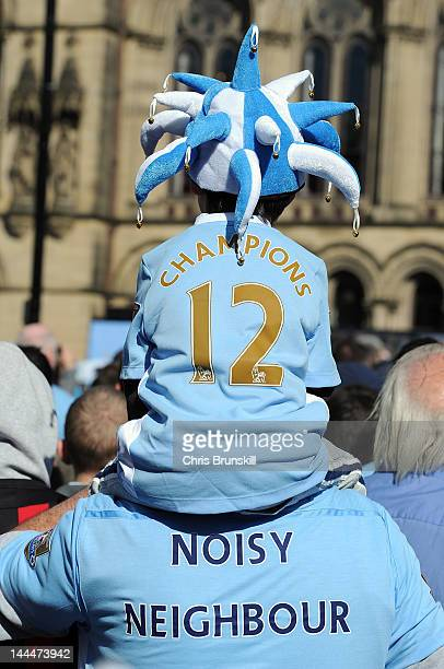Manchester City fans wear shirts displaying the messages 'Champions' and 'Noisy Neighbour' as they look on in front of Manchester Town Hall before...