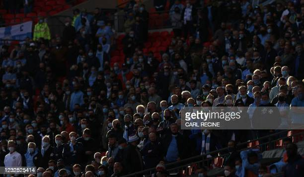 Manchester City fans wearing a protective face coverings to combat the spread of the coronavirus, look on during the English League Cup final...