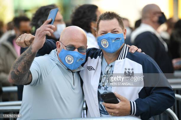 Manchester City fans wearing face coverings react as they queue to show their negative test result for Covid-19, as they arrive at Wembley Stadium to...