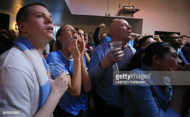 Manchester City football fans react as they watch the English Premier League football match between Manchester City and Manchester United in a pub...