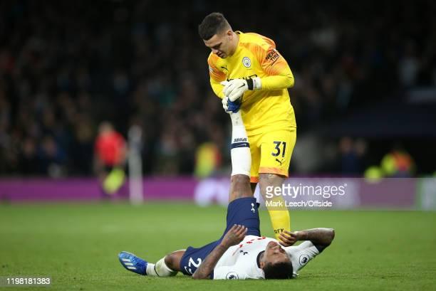 Manchester City goalkeeper Ederson sportingly attends to cramp victim Steven Bergwijn of Tottenham during the Premier League match between Tottenham...