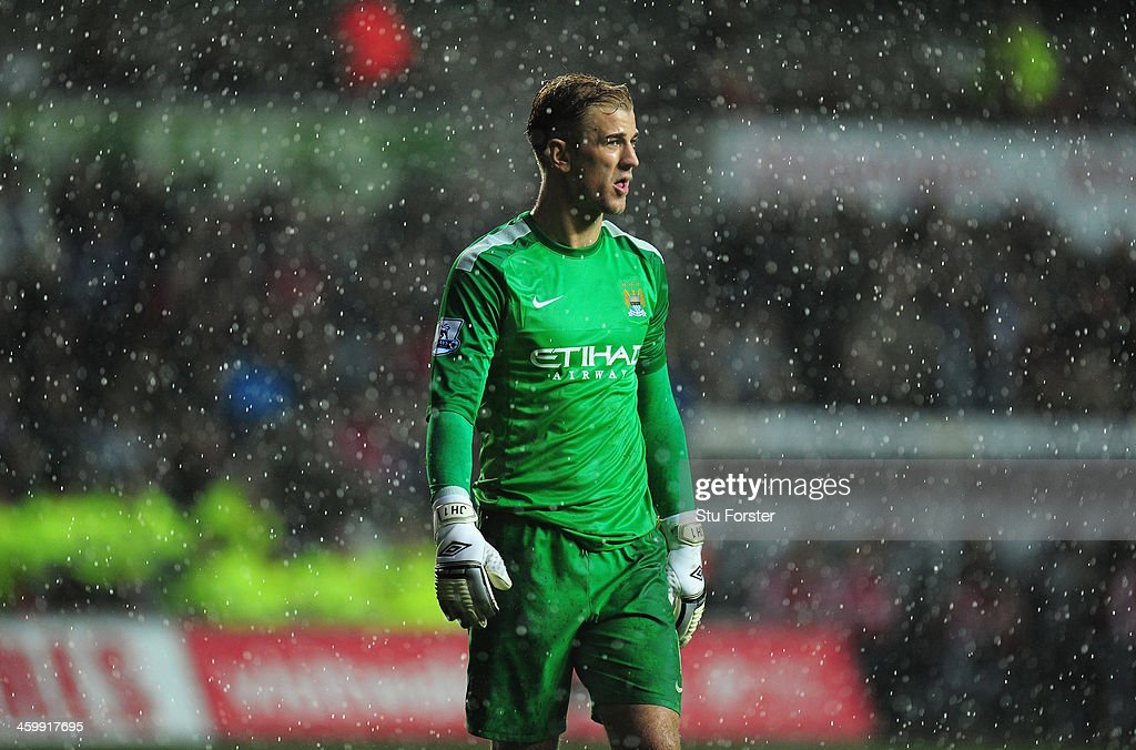 Manchester City goalkeeper Joe Hart looks on during a downpour during the Barclays Premier League match between Swansea City and Manchester City at Liberty Stadium on January 1, 2014 in Swansea, Wales.