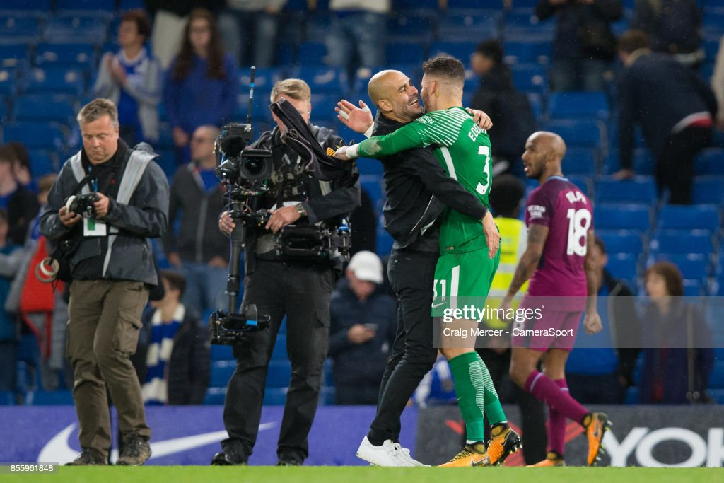Manchester City manager Josep Guardiola celebrates his sides victory with Ederson at the final whistle during the Premier League match between Chelsea and Manchester City at Stamford Bridge on September 30, 2017 in London, England.