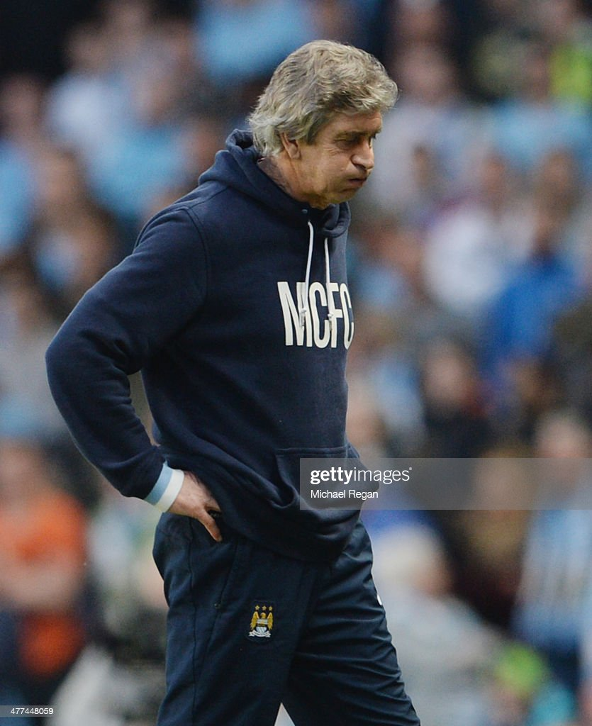 Manchester City manager Manuel Pellegrini looks dejected during the FA Cup Quarter-Final match between Manchester City and Wigan Athletic at the Etihad Stadium on March 9, 2014 in Manchester, England.