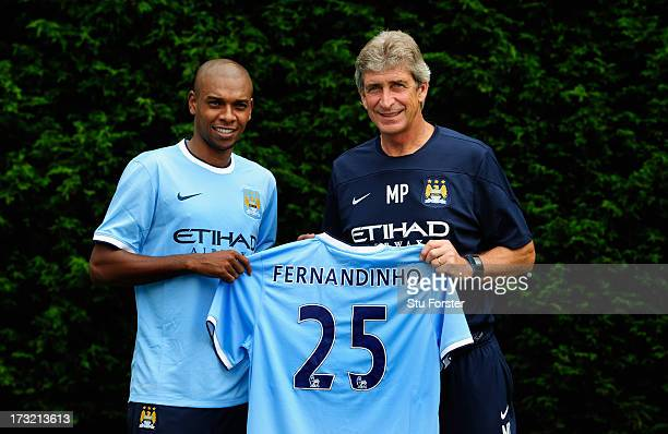 Manchester City manager Manuel Pellegrini poses with a team shirt with new player Fernandinho after their first media conference at Carrington...