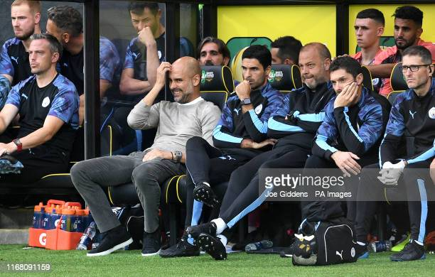 Manchester City manager Pep Guardiola and his backroom staff on the bench during the Premier League match at Carrow Road, Norwich.