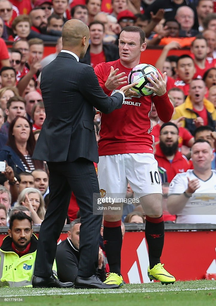 Manchester City Manager Pep Guardiola and Wayne Rooney of Manchester United argue over the ball during the Premier League match between Manchester United and Manchester City at Old Trafford on September 10, 2016 in Manchester, England.
