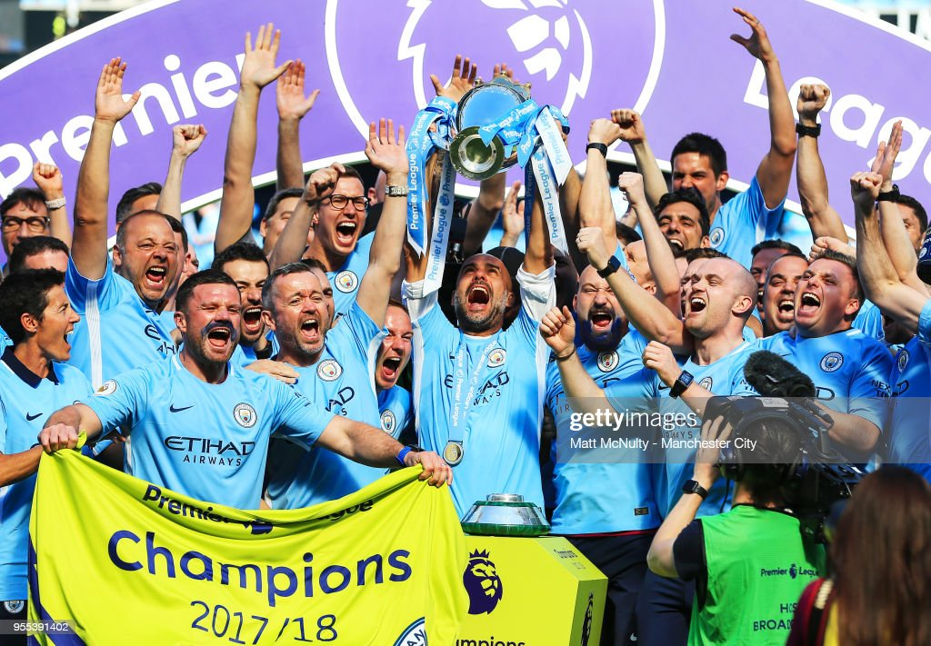 Manchester City manager Pep Guardiola celebrates with his coaching staff by lifting his first Premier League title after the Premier League match between Manchester City and Huddersfield Town at Etihad Stadium on May 6, 2018 in Manchester, England.