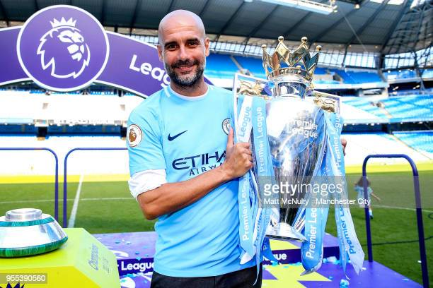 Manchester City manager Pep Guardiola celebrates with the Premier League trophy after the Premier League match between Manchester City and...