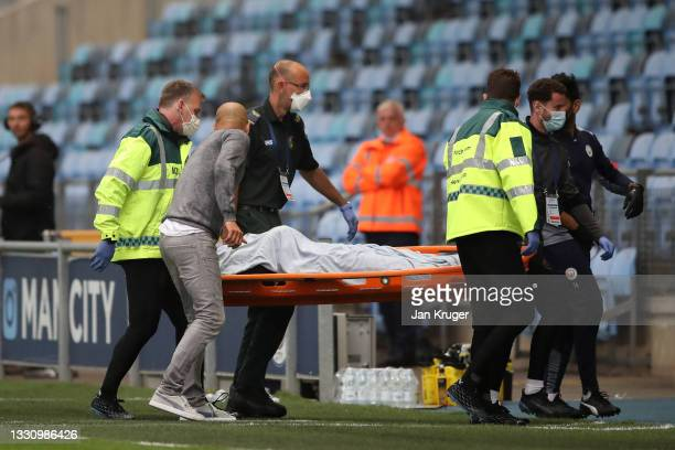 Manchester City manager Pep Guardiola checks on Ciaran Slicker of Manchester City as he is stretchered off during a pre-season friendly match between...