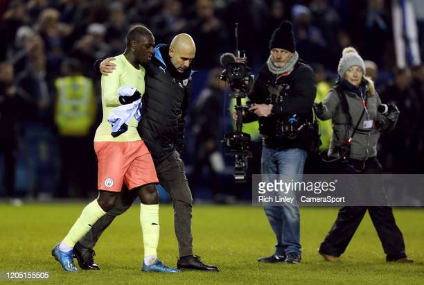 Manchester City manager Pep Guardiola embraces Benjamin Mendy at the final whistle following the FA Cup Fifth Round match between Sheffield Wednesday...