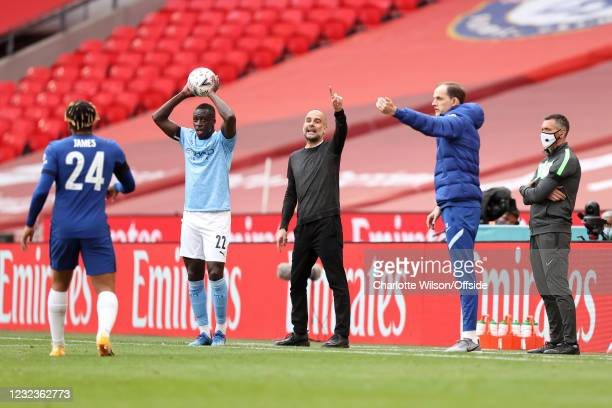 Manchester City manager Pep Guardiola gestures alongside Chelsea manager Thomas Tuchel as Benjamin Mendy of Manchester City takes a throw-in during...
