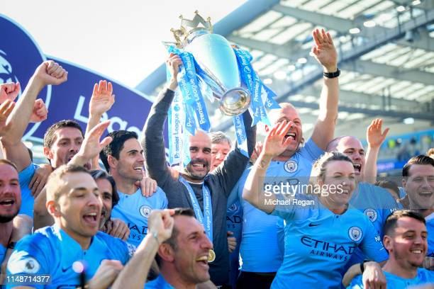 Manchester City manager Pep Guardiola holds the Premier League trophy with backroom staff during the Premier League match between Brighton Hove...
