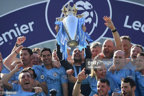 Manchester City manager Pep Guardiola holds the winner's trophy aloft after the Premier League match between Brighton Hove Albion and Manchester City...