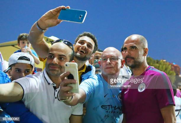 Manchester City manager Pep Guardiola interacts with fans during the training session on March 16 2018 in Abu Dhabi United Arab Emirates