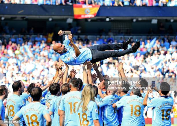 Manchester City manager Pep Guardiola is thrown in the air by his coaching staff in celebration after lifting his first Premier League title after...