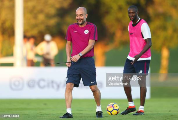 Manchester City manager Pep Guardiola jokes with Yaya Toure during the training session on March 16 2018 in Abu Dhabi United Arab Emirates
