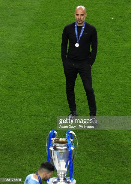 Manchester City manager Pep Guardiola looks on at the trophy after the final whistle during the UEFA Champions League final match held at Estadio do...