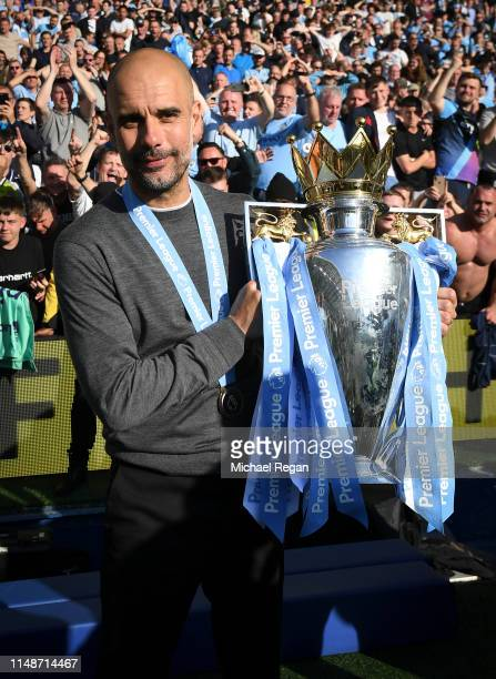 Manchester City manager Pep Guardiola poses with the Premier League trophy after the Premier League match between Brighton Hove Albion and Manchester...