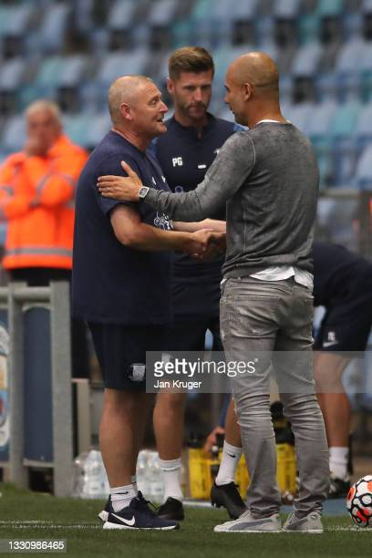 Manchester City manager Pep Guardiola shakes hands with Preston North End manager Frankie McAvoy during a pre-season friendly match between...