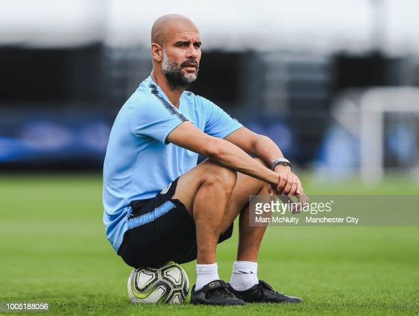 Manchester City manager Pep Guardiola sits on a football to watch the training session at New York City CFA on July 23 2018 in New York New York