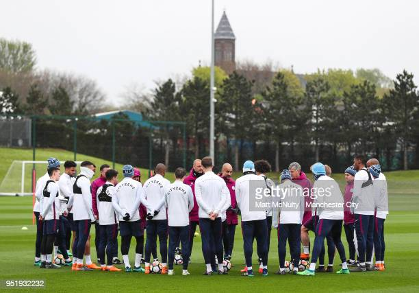 Manchester City' manager Pep Guardiola speaks to his players during training at Manchester City Football Academy on April 27 2018 in Manchester...