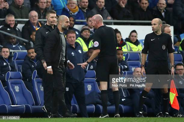 Manchester City manager Pep Guardiola speaks to match referee Lee Mason on the touchline during the Emirates FA Cup Fourth Round match at Cardiff...