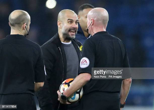 Manchester City manager Pep Guardiola speaks with match referee Lee Mason after the Emirates FA Cup Fourth Round match at Cardiff City Stadium