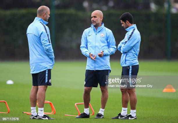 Manchester City manager Pep Guardiola talks with coaches Mikel Arteta and Rodolfo Borrell during training at Manchester City Football Academy on July...