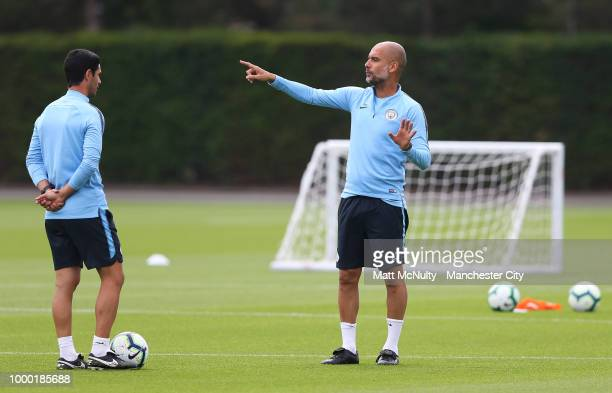 Manchester City manager Pep Guardiola talks with Mikel Arteta during training at Manchester City Football Academy on July 16 2018 in Manchester...