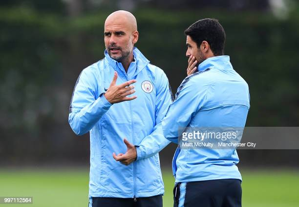 Manchester City manager Pep Guardiola talks with Mikel Arteta during training at Manchester City Football Academy on July 12 2018 in Manchester...