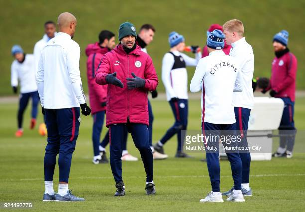 Manchester City manager Pep Guardiola talks with Vincent Kompany David Silva and Kevin de Bruyne during the training session at Manchester City...