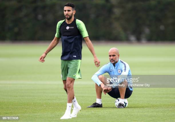 Manchester City manager Pep Guardiola watches Riyad Mahrez during training at Manchester City Football Academy on July 13 2018 in Manchester England