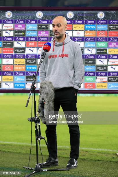 Manchester City manager Pep Guardiola wears a hoodie bearing the 'Open Arms' logo as he gives a television interview after the Premier League match...