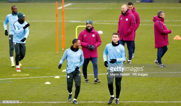 Manchester City manager Pep Guardiola with Manchester City's Raheem Sterling and Manchester City's Aymeric Laporte during the training session at the...