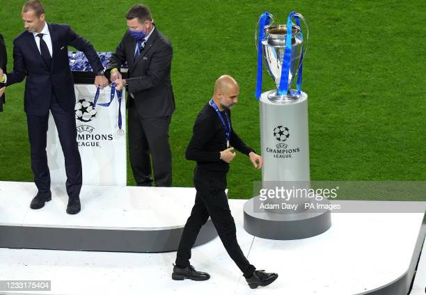 Manchester City manager Pep Guardiola with the runners up medal as he walks past the trophy after the final whistle during the UEFA Champions League...