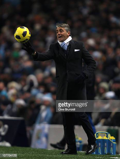 Manchester City manager Roberto Mancini catches a stray ball during the Barclays Premier League match between Manchester City and Everton at City of...