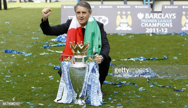 Manchester City manager Roberto Mancini celebrates with the trophy following the Barclays Premier League match at the Etihad Stadium, Manchester.