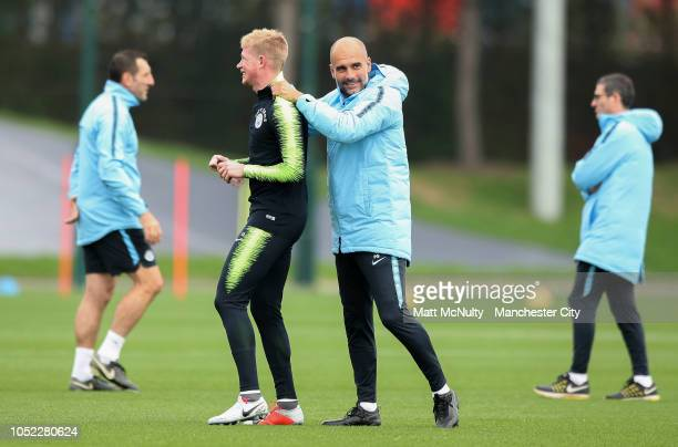 Manchester City manager shares a joke with Kevin de Bruyne during the training session at Manchester City Football Academy on October 16 2018 in...