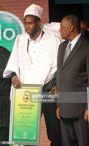 Manchester City midfielder Yaya Toure holds a placard beside CAF President Issa Hayatou after being declared winner of CAF African Footballer of the...