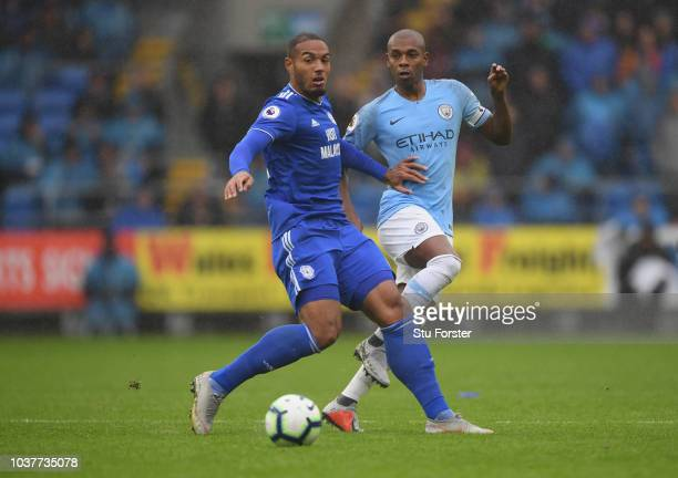 Manchester City player Fernandinho is challenged by Kenneth Zohore of Cardiff during the Premier League match between Cardiff City and Manchester...