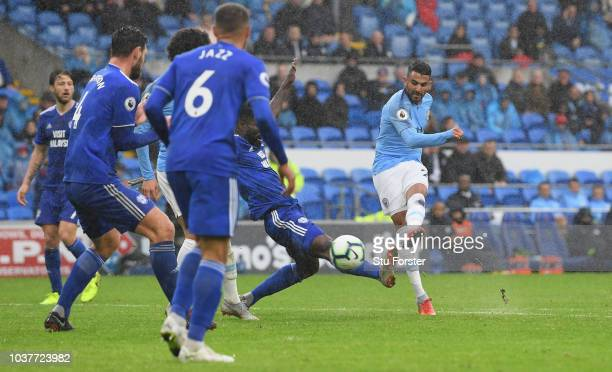 Manchester City player Riyad Mahrez shoots to score his second goal and City's 5th goal during the Premier League match between Cardiff City and...