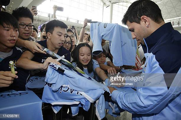 Manchester City player Sergio Aguero signs autographs memorabilia for Manchester City fans at Hong Kong Airport shortly after the team arrives to...