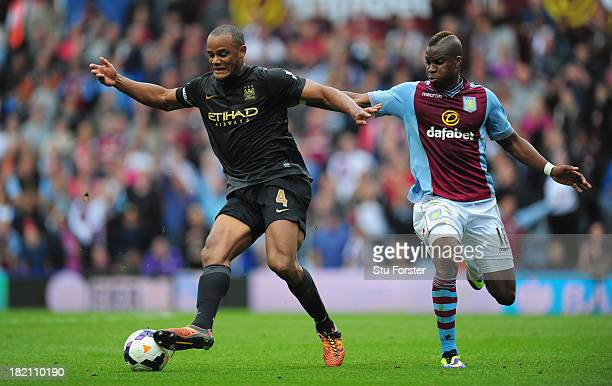 Manchester City player Vincent Kompany battles for the ball with Yacouba Sylla during the Barclays Premier League match between Aston Villa and...