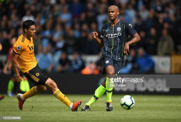 Manchester City player Vincent Kompany in action with Wolves forward Raul Jiminez during the Premier League match between Wolverhampton Wanderers and...