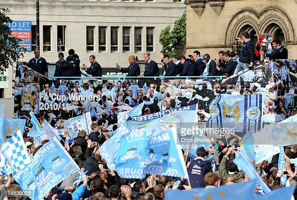 Manchester City players celebrate on board an opentop bus during the Manchester City FA Cup Winners Parade at Manchester Town Hall on May 23 2011 in...