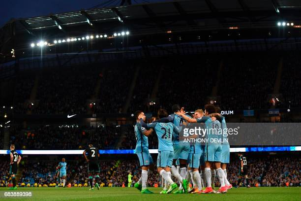 Manchester City players celebrate their third goal scored by Manchester City's Ivorian midfielder Yaya Toure during the English Premier League...