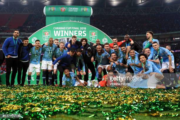 Manchester City players celebrate victory with the trophy after the Carabao Cup Final between Chelsea and Manchester City at Wembley Stadium on...
