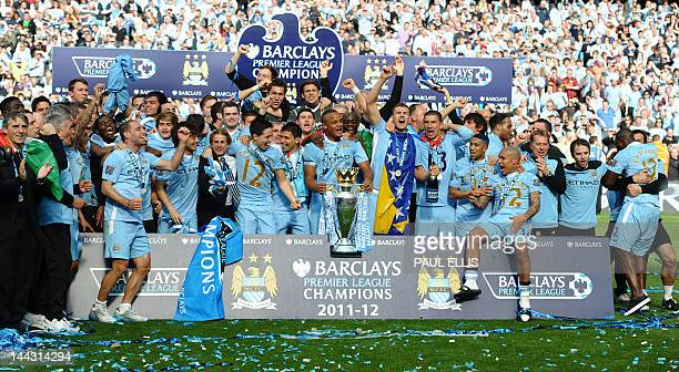 Manchester City players celebrate with the Premier League trophy after their 32 victory over Queens Park Rangers in the English Premier League...